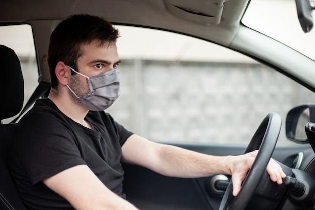 男性の運転手が医療用灰色のマスクに座っています。