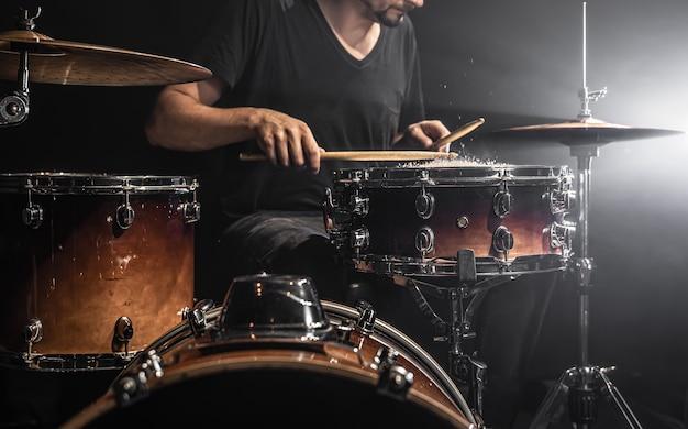 남성 드러머는 어두운 방에서 물이 튀는 작은 북에서 드럼 스틱을 연주합니다.