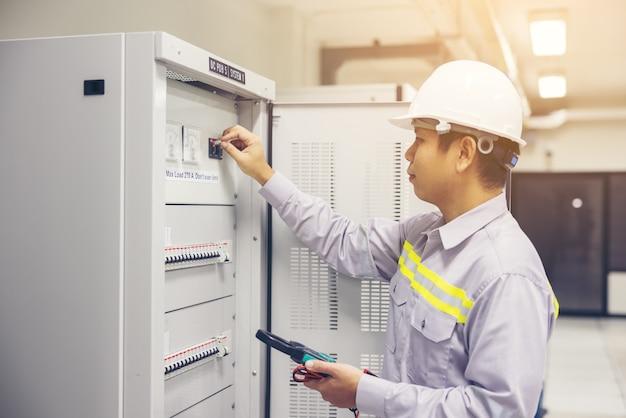 남성 전기 기사는 배전반 전기 단자 정션 박스에서 작동합니다.