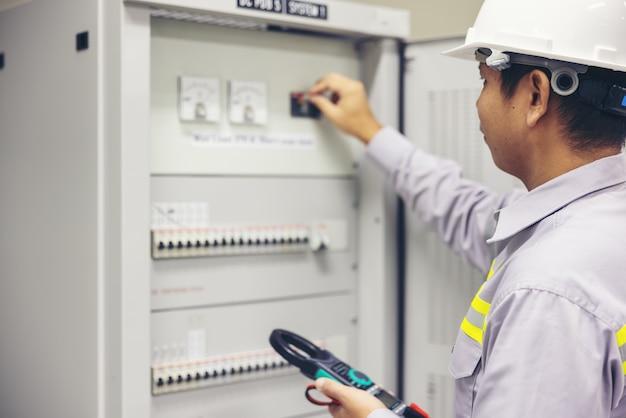 男性の電気技師が配電盤の電気端子ジャンクションボックスで作業します