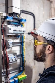 남성 전기 기사는 전기 연결 케이블이 있는 배전반에서 작동합니다.