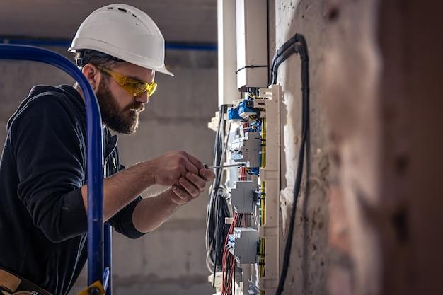 Электрик-мужчина работает в распределительном щите с электрическим соединительным кабелем.