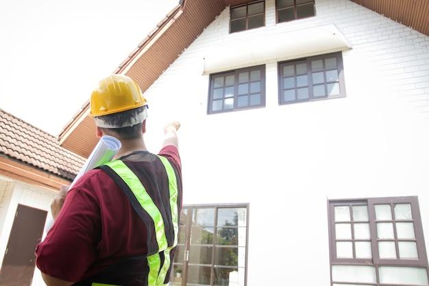 男性エンジニアが家を検査して顧客に届けます。家の前に立って、正面を指しています。住宅建設住宅のコンセプト