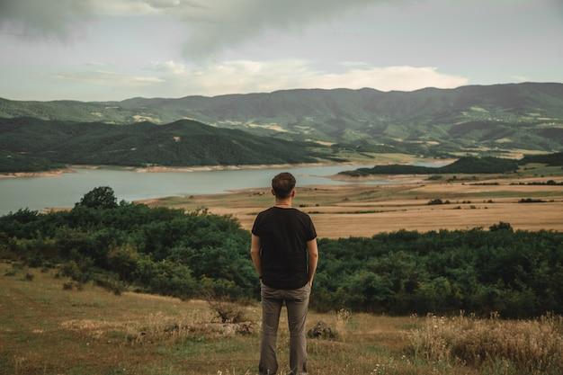 後ろから撮影した美しい景色を楽しむ男性