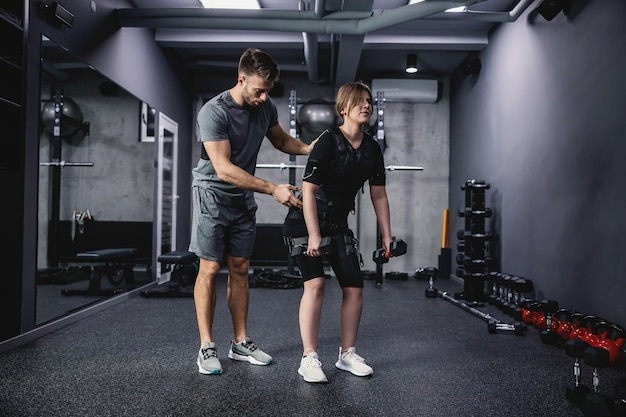 남성 피트니스 강사는 ems 기술을 위한 검은색 특수 수트를 입고 여성을 도우면서 현대적인 체육관 개념에서 안정성 등 및 팔 운동을 수행합니다. 훈련의 혁명, 신체 재활