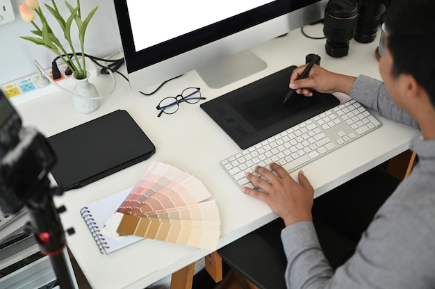 워크 스테이션에서 태블릿을 사용하는 남성 그래픽 디자이너.