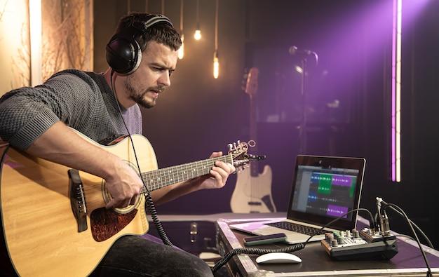 남성 기타리스트가 사운드 믹서에 연결된 헤드폰으로 기타를 연주합니다. 노트북 모니터의 디지털 파형.