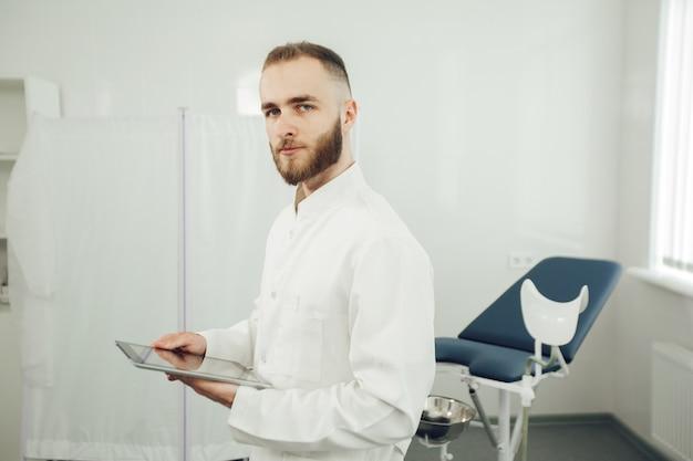 男性の婦人科医がオフィスに一人でいて、タブレットを持ってカメラを見ています。現代医学の概念
