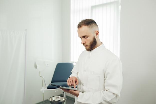 男性の婦人科医がオフィスに一人でいて、タブレットを持って検査結果を読んでいます。現代医学の概念