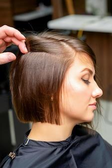 남성 미용사가 미용실에서 젊은 여성의 머리카락을 곧게 펴고 있습니다.