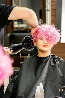 미용실에서 타격 건조기로 여성 고객의 남성 미용사 전문 건조 세련된 핑크색 머리카락