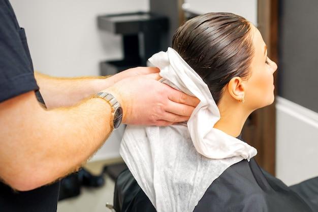 ビューティーサロンでシャンプーした後、男性の美容師の手が女性のクライアントの髪を白いタオルで拭きます