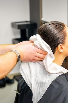 男性の美容師の手が美容院でシャンプーした後、白いタオルで女性のクライアントの髪を拭きます