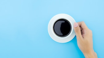 A male hand hold a cup of coffee on blue background, top view.