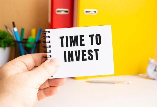 男性の手は、「投資する時間」というテキストが書かれたメモ帳をバネに持っています。事務所スペース。