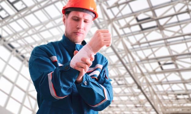 붕대, 사고 부상, 응급 처치 도움으로 제복을 입은 남성 산업 노동자
