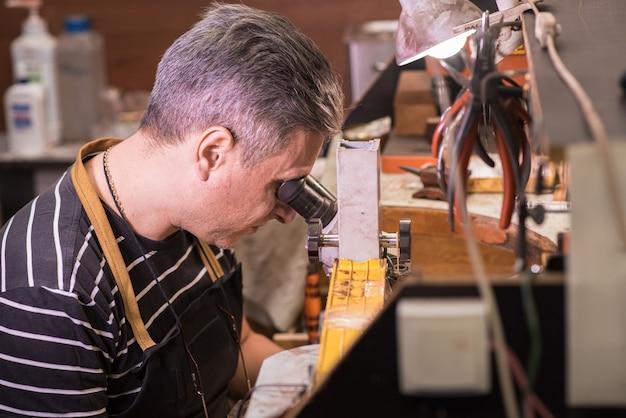 Ювелир-мужчина смотрит в микроскоп и фиксирует драгоценный камень на кулоне.