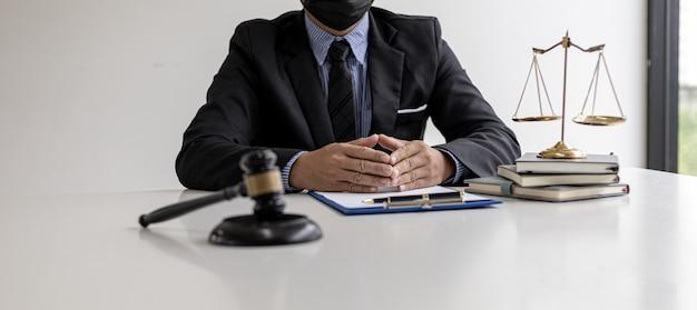 男性弁護士が彼の事務所の小さなハンマーでテーブルの上に座って、法廷の裁判官の机を打ち負かした。と正義のスケール、弁護士は、クライアントが被告と署名するために使用するための契約を起草しています