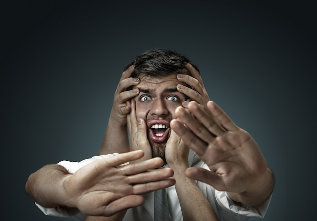 어두운 벽에 자신의 생각처럼 손으로 둘러싸인 남성 모델 무료 사진