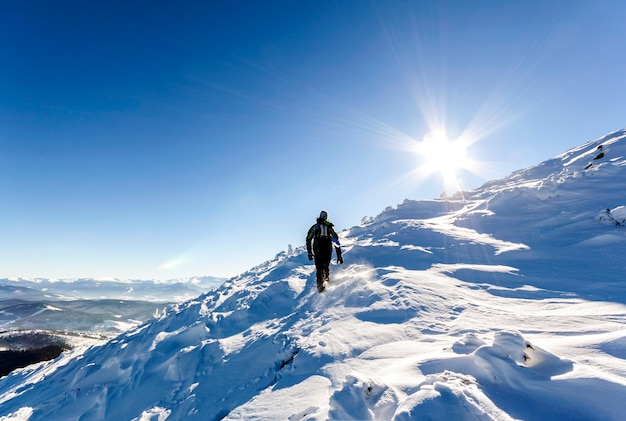 빙하에 오르막을 걷는 남성 산악인. 등산객은 화창한 겨울 날 눈 덮인 산 꼭대기에 도달합니다.