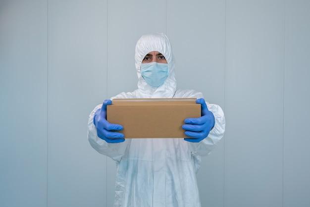 スーツの保護具を着た男性看護師がコロナウイルスまたはコビッド19の医薬品を届ける