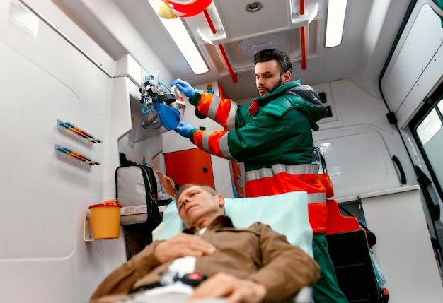 制服を着た男性の救急医療員は、現代の救急車の担架に横たわっている高齢の患者を助けるために酸素マスクを探しています。