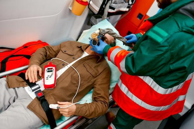 制服を着た男性の救急医療員は、酸素濃度計を備えた人工呼吸器を装着して、現代の救急車のパルスオキシメータを備えた担架に横たわっている高齢の患者を支援します。