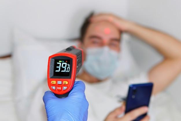 非接触温度計で体温を測定している男性。病室の保護マスクを着用した患者。