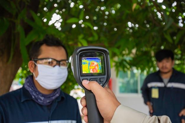 測定されている男性は、非接触型赤外線で体温をスキャンします