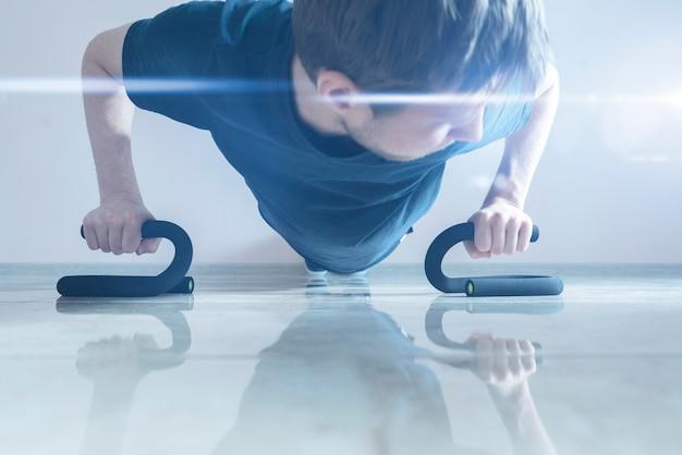 Мужчина делает отжимания на полу, делая фигуру подтянутой, делает упражнения для здоровья