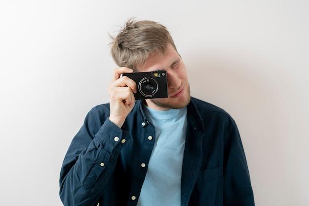 ヴィンテージカメラを持って設定を調整する男性、昔ながらのトレンド