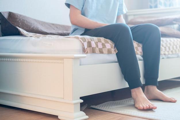 Мужчина сидит на кровати с ногами на полу, просыпается утром