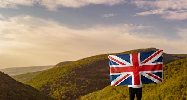Мужчина с национальным флагом великобритании, патриотизмом и концепцией свободы на открытом воздухе