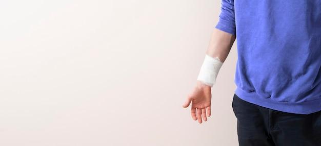 腕に白い包帯を巻いて、医学的な痛みと怪我をして、傷ついた男性