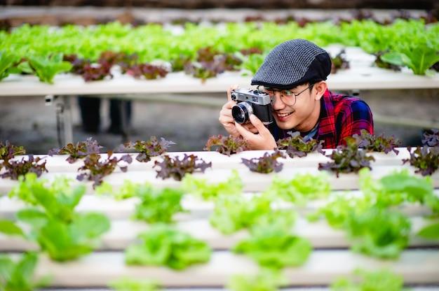 남성 사진 작가가 샐러드 정원에서 사진을 찍고 사진을 즐기고 있습니다.