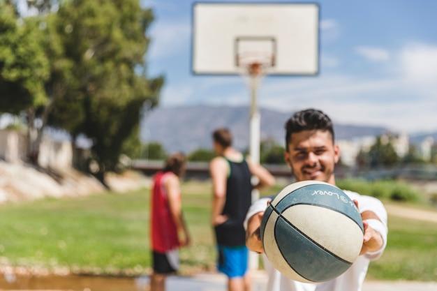 カメラの前にバスケットボールを持っている男性プレーヤー