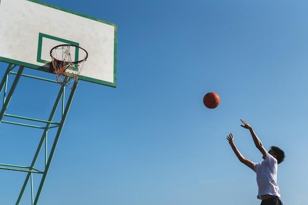농구 후프에 공을 던지는 남자 선수