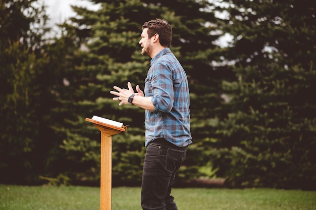 表彰台の近くに立って聖書を読んでいる男性