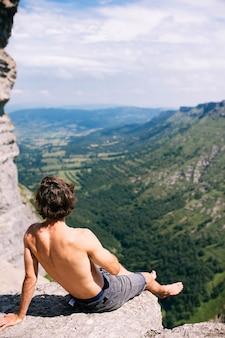바위 절벽 위에 앉아 산과 녹지의 아름다운 전망을 즐기는 남성