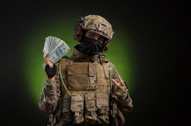 お金で暗い背景に武器を持った軍服の男性兵士