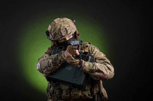어두운 배경에 무기를 들고 군복을 입은 남성 군인