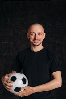 男性のスポーツ教師が暗い背景に立って、サッカーボールを持って、カメラを見て、笑顔