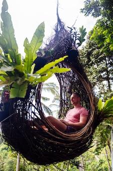 男性観光客がバリ島の木の大きな鳥の巣に座っています。