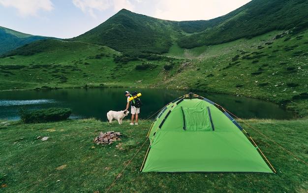 湖のほとりのテントの近くに、バックパックとゴム製のマットを持った男性観光客が立っています。緑の山のふもとに犬と一緒に若いハイカー。旅行、休暇、観光。