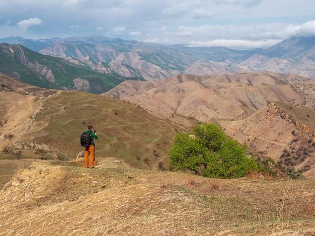 スマートフォン付きのバックパックを持った男性観光客が美しい山の風景を撮影します。