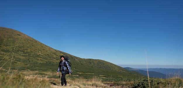 大きなバックパックを背負った男性観光客が山腹を登る