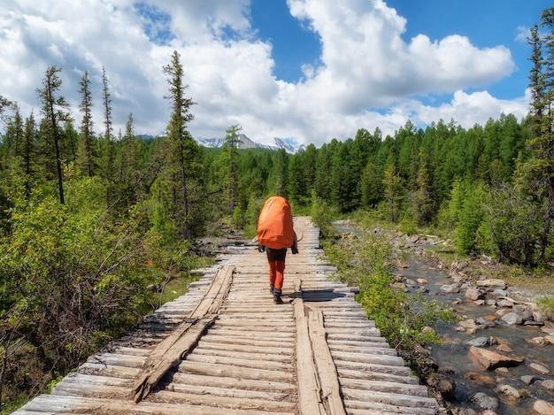 大きなオレンジ色のバックパックを持った男性観光客が、針葉樹林と遠くの山々を背景に古い木製の橋を歩いています。