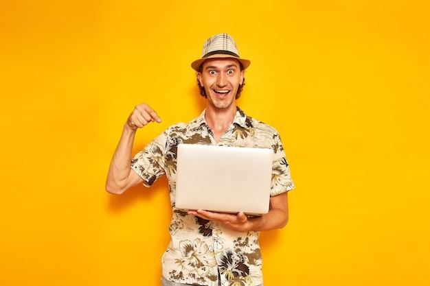 노트북을 손에 들고 있는 남성 관광객은 노란색 배경에 격리된 메시지를 받고 기뻐한다