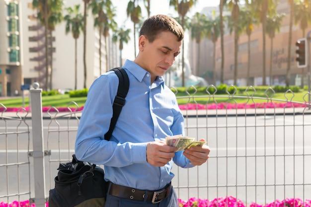 男性の旅行者が彼の手で保持していると、街の通りでさまざまな国からの紙幣を考えています。