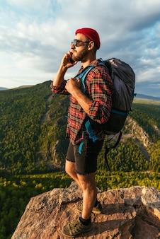 Путешественник в красной шляпе с рюкзаком разговаривает по телефону на фоне гор. мужчина в походной одежде разговаривает по смартфону на закате в горах. телефонный разговор